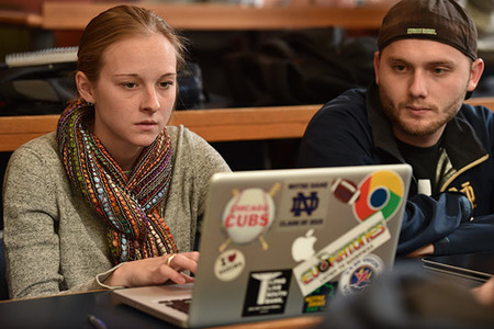 Two psychology students working together on a laptop in the classroom